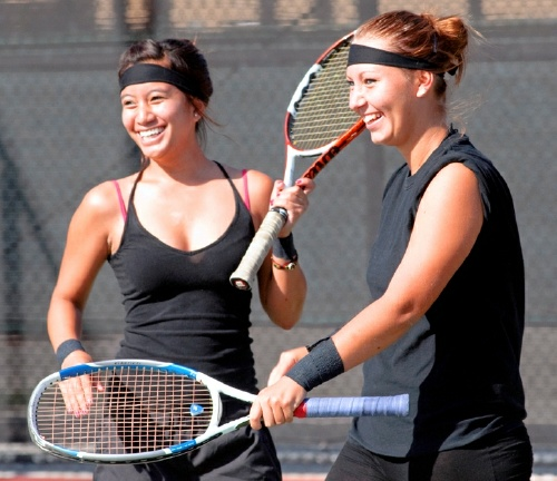 Pictured: Cal State L.A. women's tennis team members Jillian Sangria (left) and Linda Majzlikova (right) enjoy a point during an intra-squad practice.