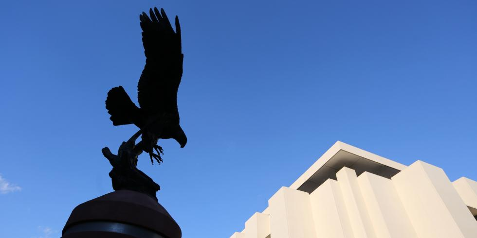 Silhouette of Golden Eagle statue against blue sky, with library in background