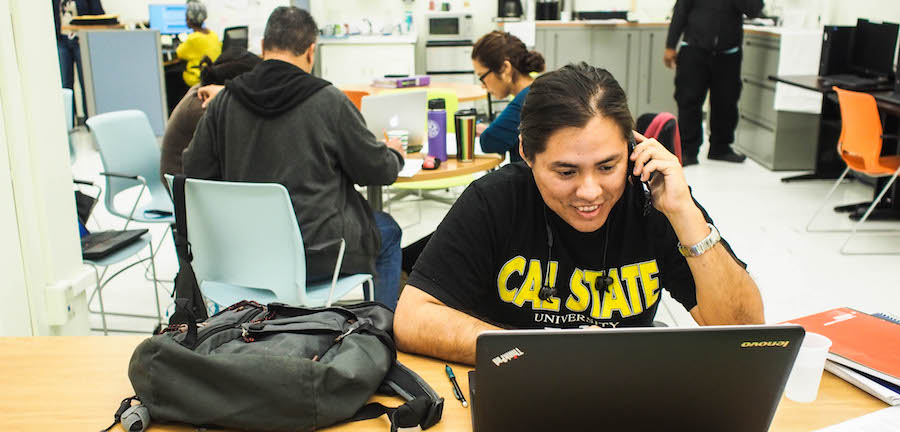 A graduate student wearing a Cal State LA T-shirt, sitting at a table with a laptop while talking on a cell phone