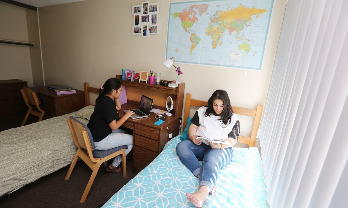 Two female students studying in their bedroom.