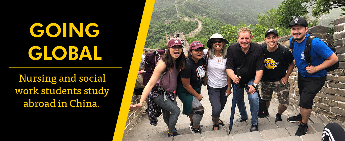 Students stand with the dean and associate dean on the Great Wall of China.