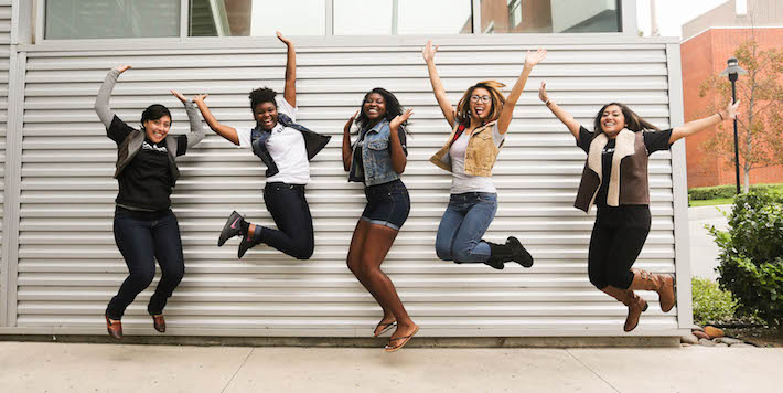 Five students in casual clothing jumping and smiling in mid air next to the metal wall of a building.