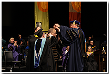 CSU Chancellor Timothy White places the Presidential Medallion upon the head of President William A. Covino.