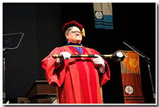 Chair of the Academic Senate and Bearer of the Mace Kevin Baaske holds the mace to lead the procession.