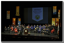 A wide picture of the platform party displays the academic regalia and colorful setting.